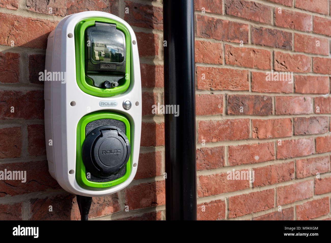 A Rolec, domestic, electric car charging point on the wall of a home. - Stock Image