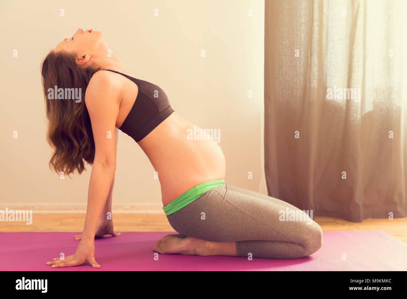 Pregnancy, yoga, people and healthy lifestyle concept - happy pregnant woman exercising at home - Stock Image