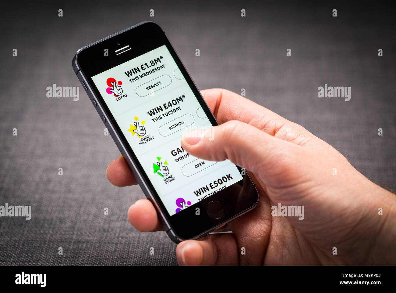 A man using The National Lottery app on an iPhone - Stock Image