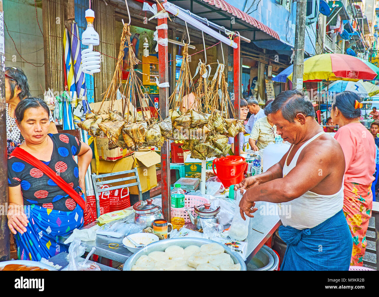 YANGON, MYANMAR - FEBRUARY 14, 2018: The market stall in Chinatown with dishes of local cuisine - banana leaf-wrapped food, dumplings and others, on F - Stock Image