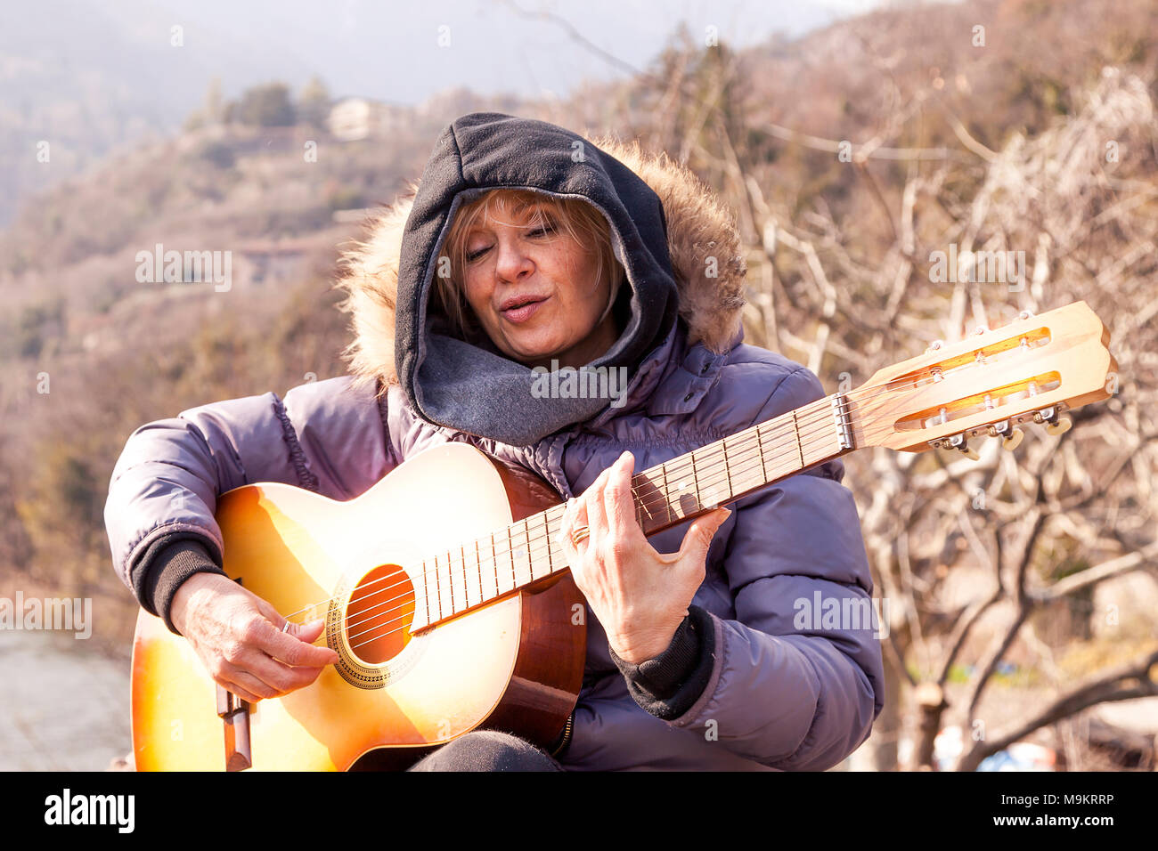 portrait mature woman playing guitar stock photos & portrait mature