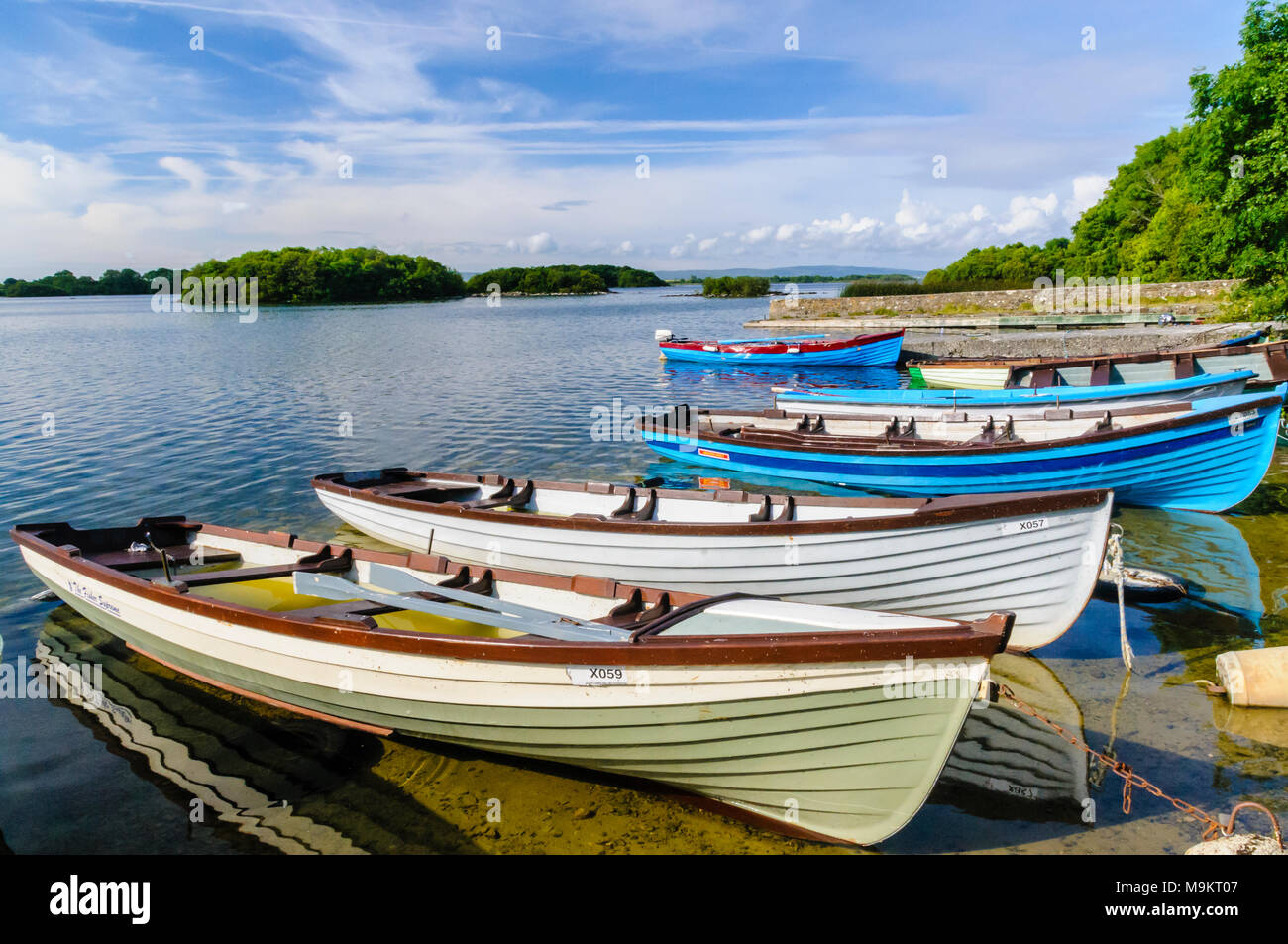 Rowing boats filled with water sit moored up at the Irish Lough Corrib, Galway, Ireland. - Stock Image