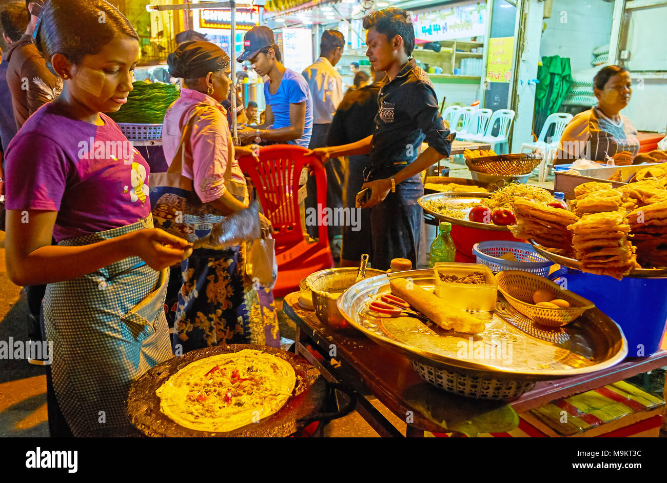 YANGON, MYANMAR - FEBRUARY 14, 2018: Young girl cooks traditional Burmese street food - pancakes with vegetables and chickpeas, crispy fried pies, Mah - Stock Image