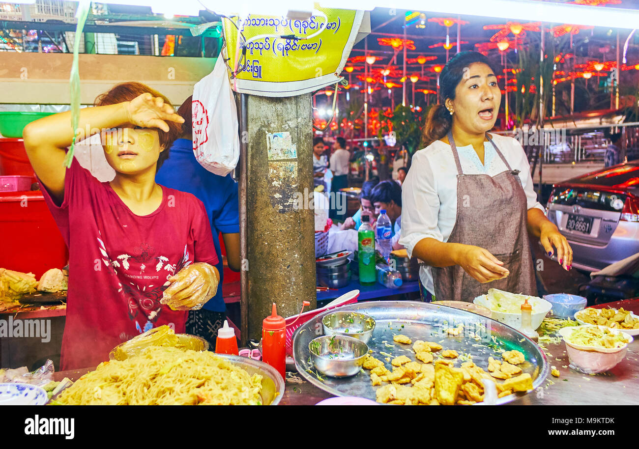 YANGON, MYANMAR - FEBRUARY 14, 2018:  The evenings are the hot time for street food vendors in Chinatown, small outdoor cafe next to Chinese Temple of - Stock Image