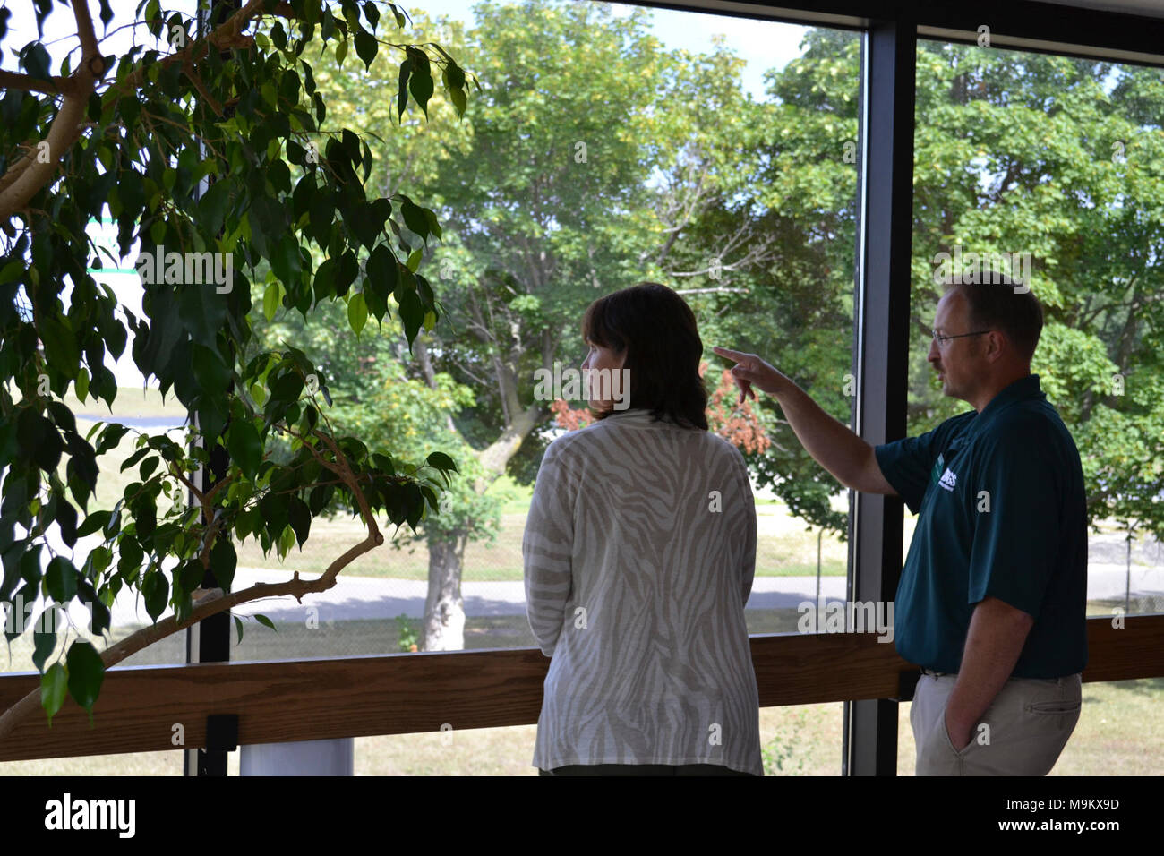 Mark Gaikowski, a research physiologist with the U.S. Geological Survey (USGS), points to the large research ponds at the Upper Midwest Environmental Sciences Center (UMESC). Rep. Betty McCollum (D-Minn.) looks on. Photo by Garrett Peterson/USFWS. - Stock Image