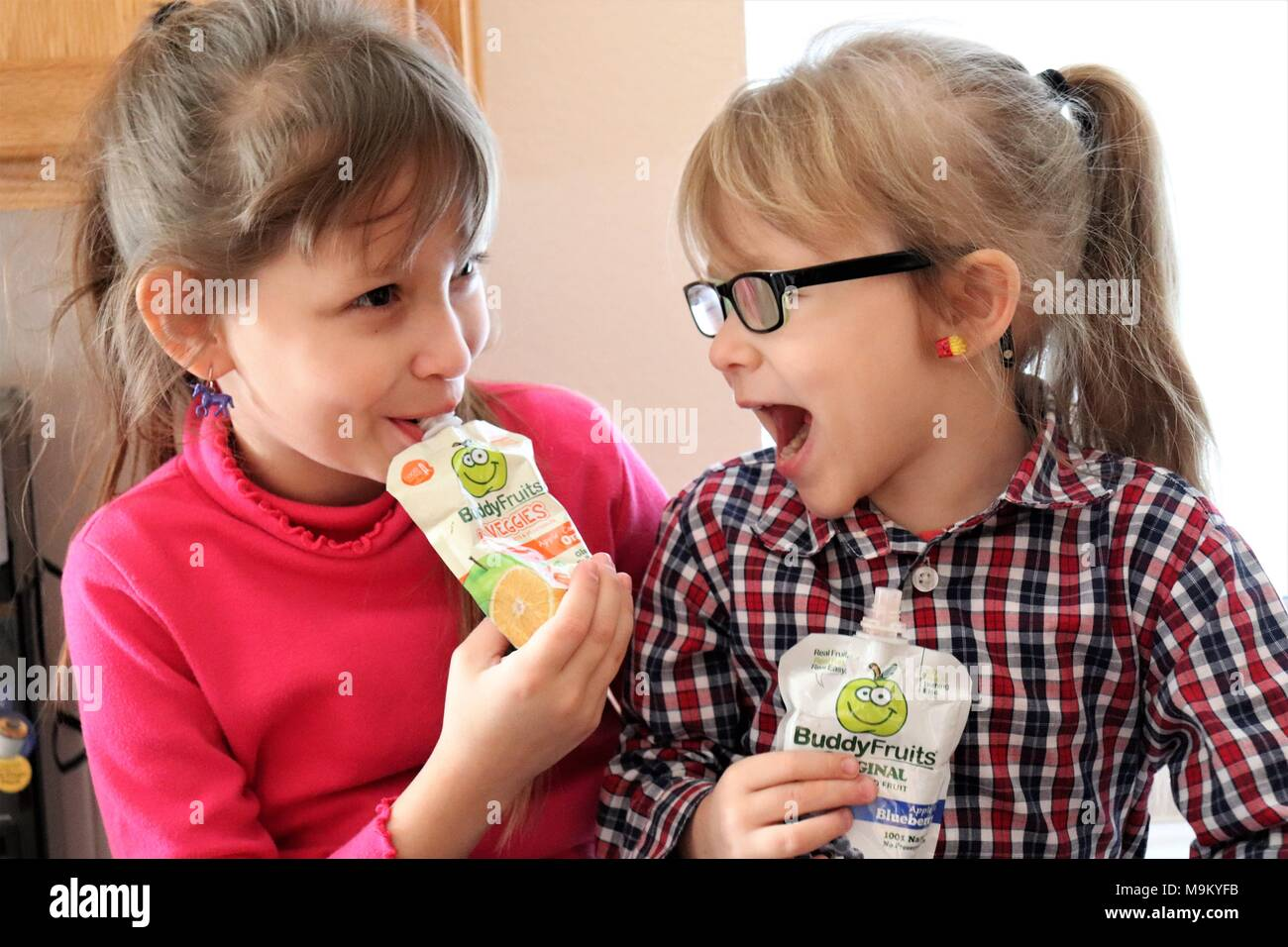 Sisters enjoying Buddy Fruits in the kitchen - Stock Image