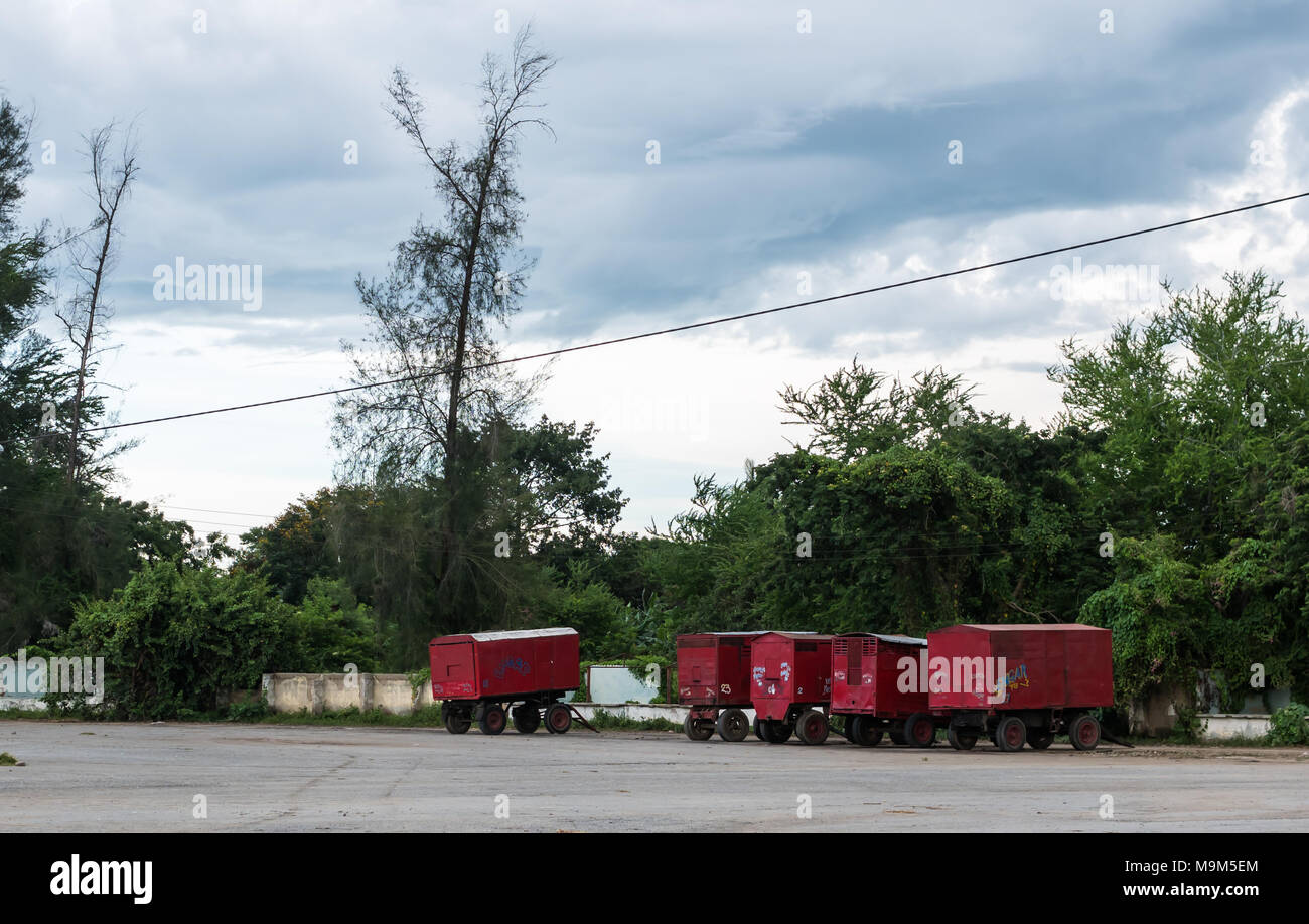 Las Tunas, Cuba - September 4, 2017: Five red trailers, with the company name EMGAR painted on the side, parked on an empty lot at the  city fairgroun - Stock Image