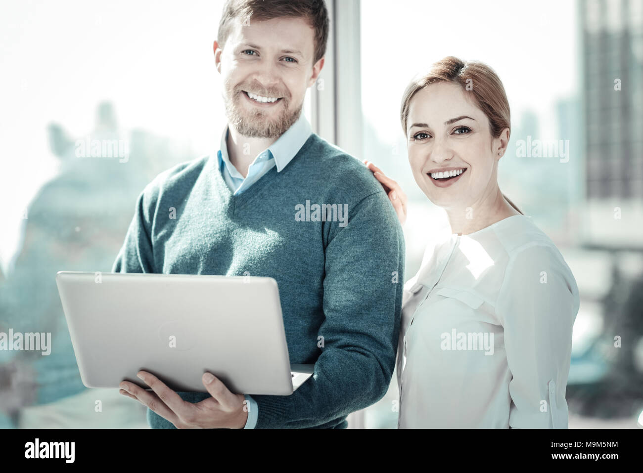 Pleasant responsible colleagues standing and smiling. - Stock Image