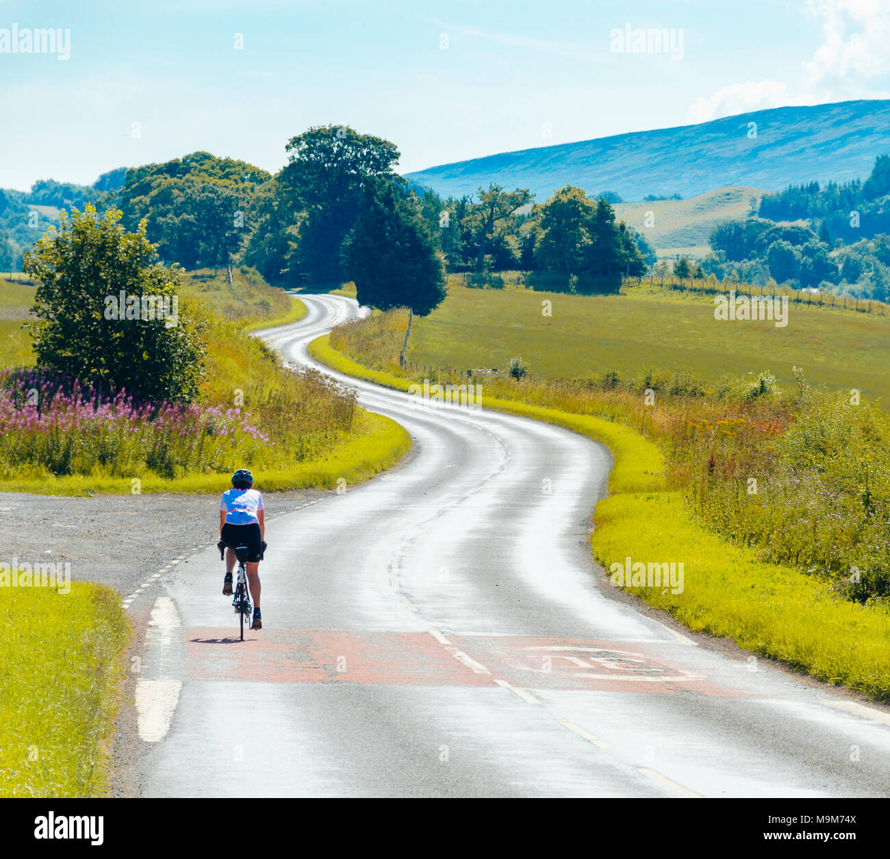 Female cyclist on the A689 outside Milton near Brampton, Cumbria with view to the North Pennines - Stock Image