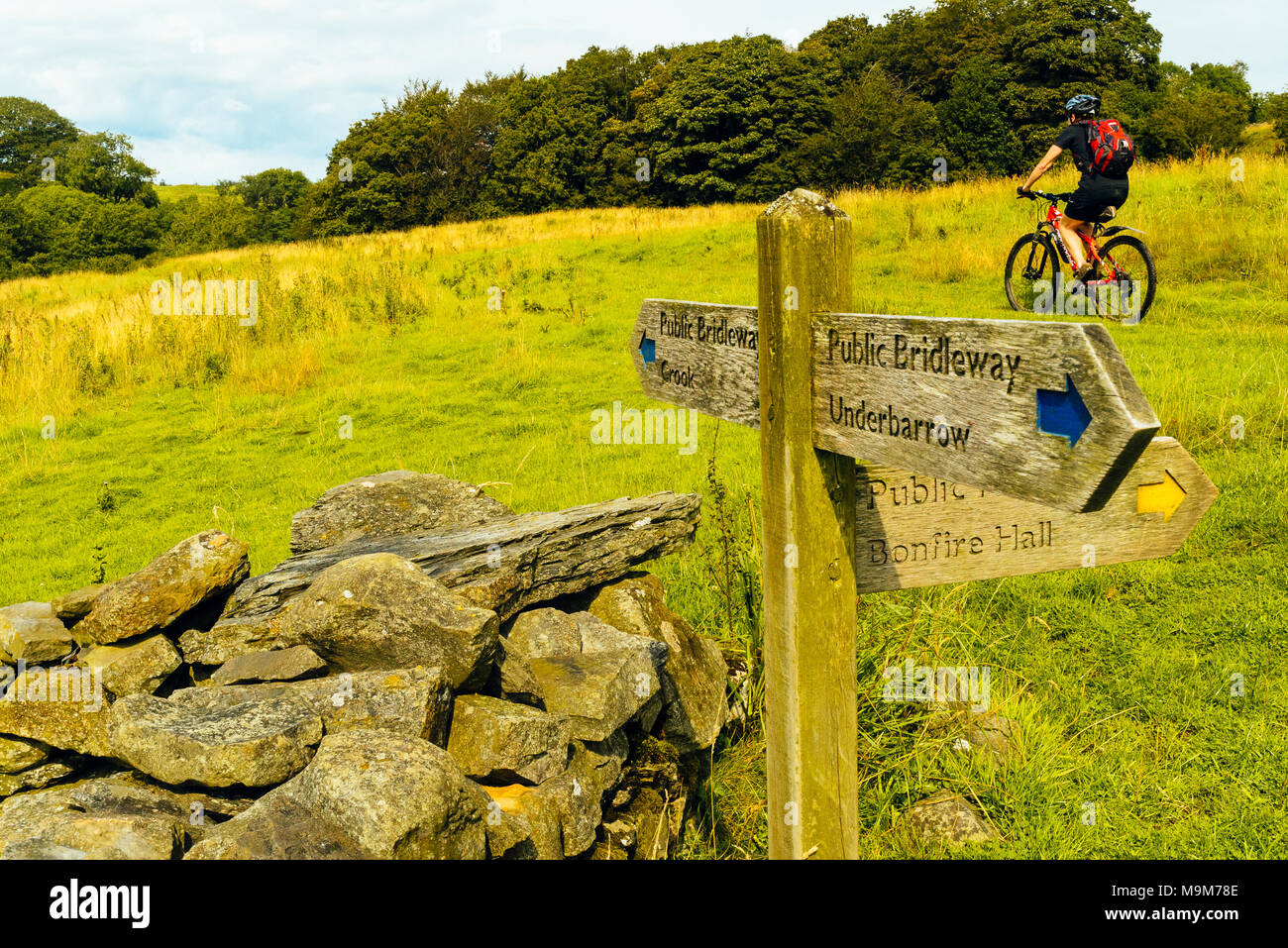 Mountain biker passing right of way signs in countryside west of Kendal, Cumbria - Stock Image