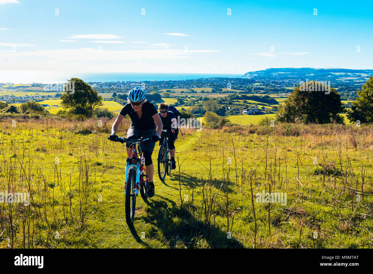 Two female cyclists climb onto Brading Down between Sandown and Ryde in the Isle of Wight, one on a mountain bike, one on a gravel bike Stock Photo