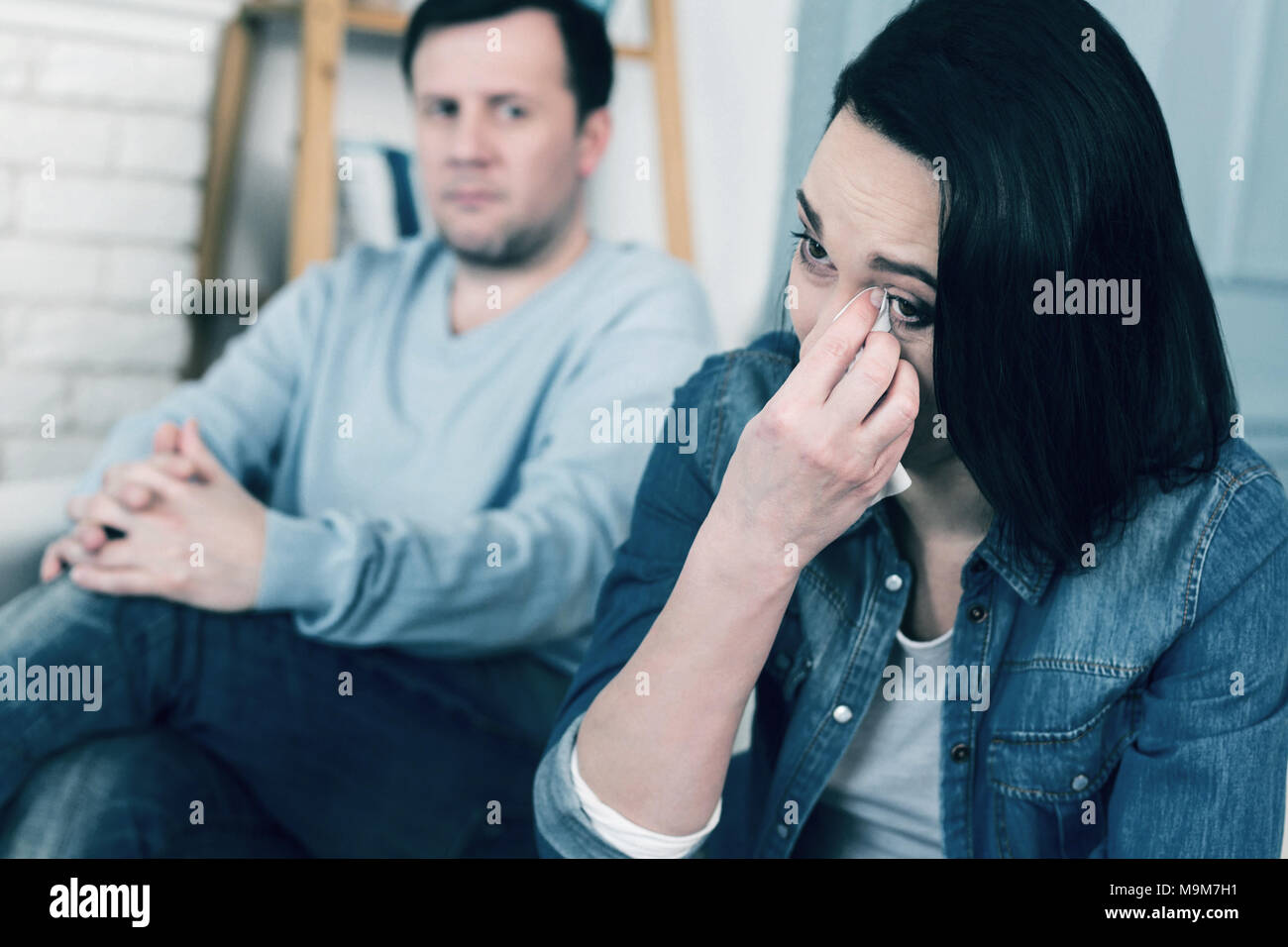 Unhappy woman wiping her tears - Stock Image