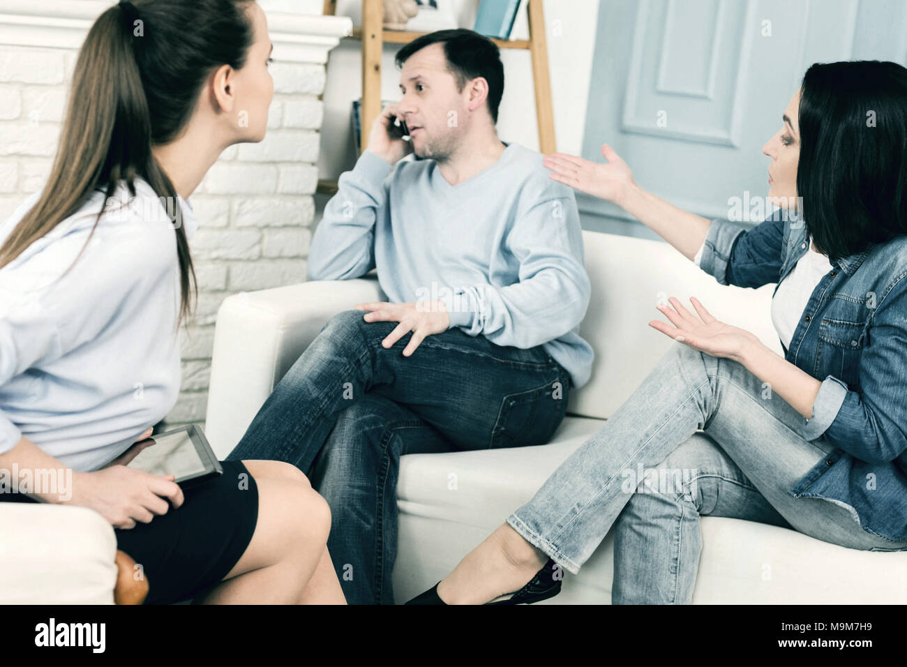Busy man talking on telephone while being at family consultation - Stock Image