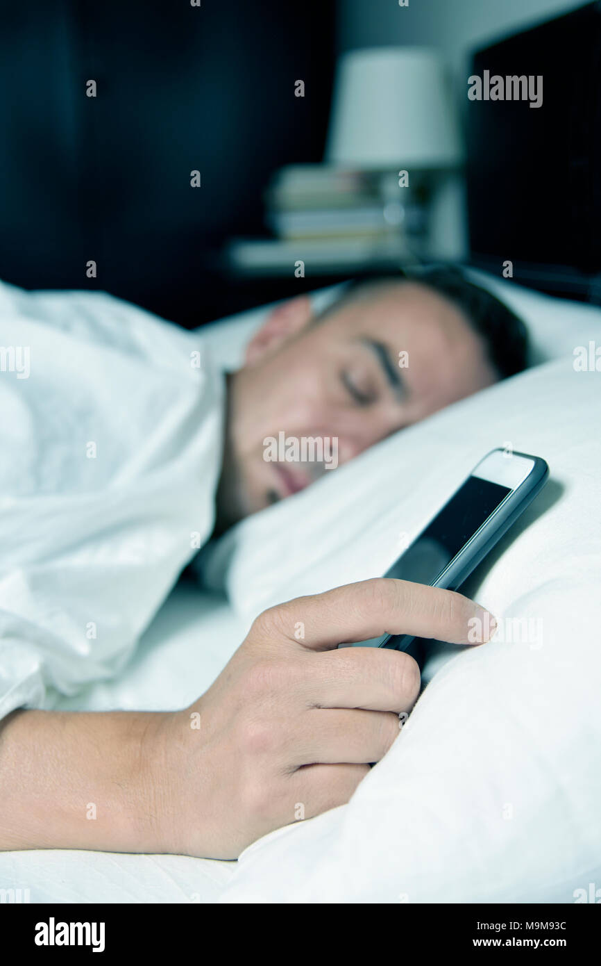 closeup of a young caucasian man lying down in bed grabbing his smartphone - Stock Image