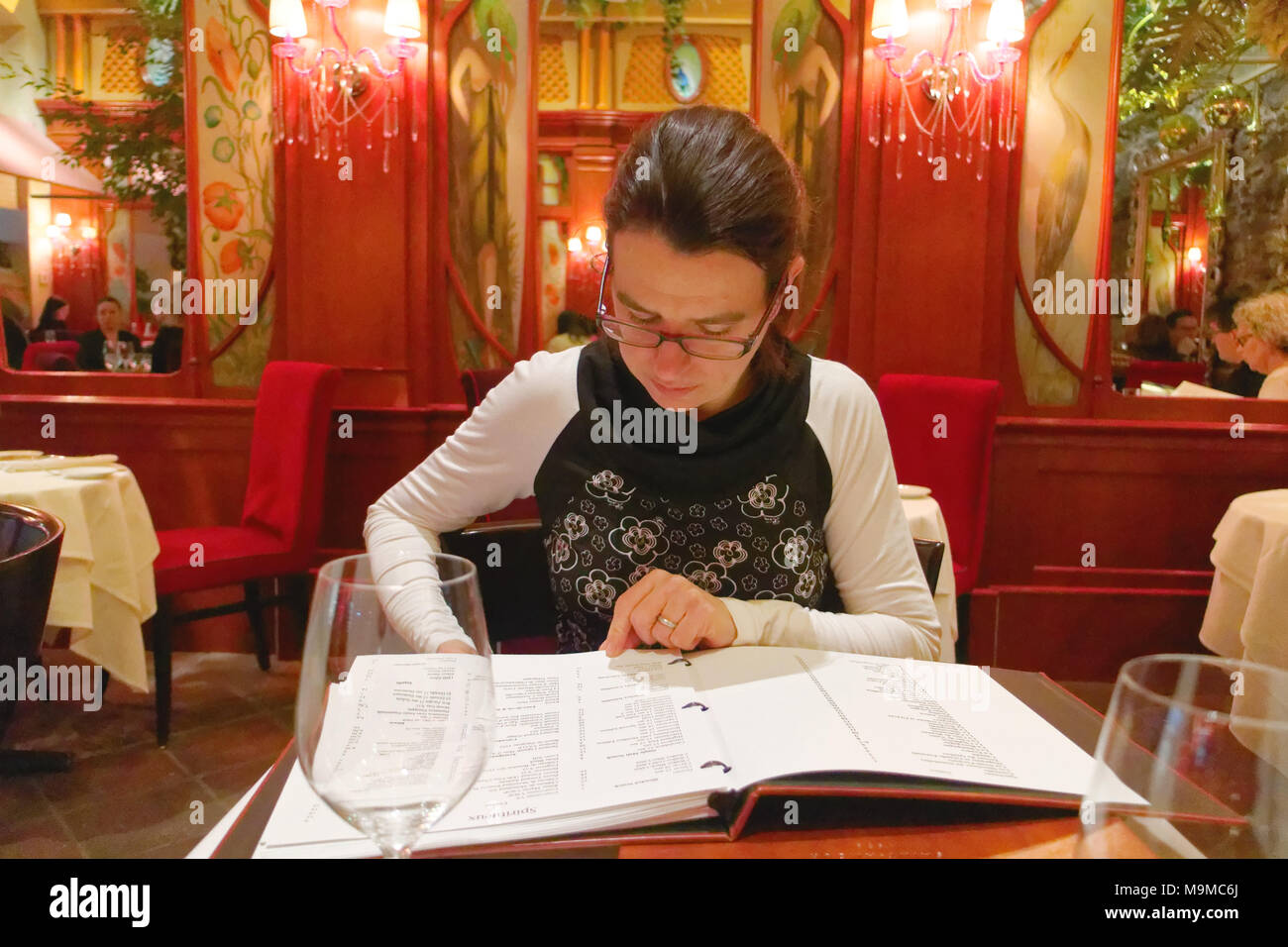 A woman looking at the wine list in the restaurant Saint Amour in Quebec City, Canada - Stock Image