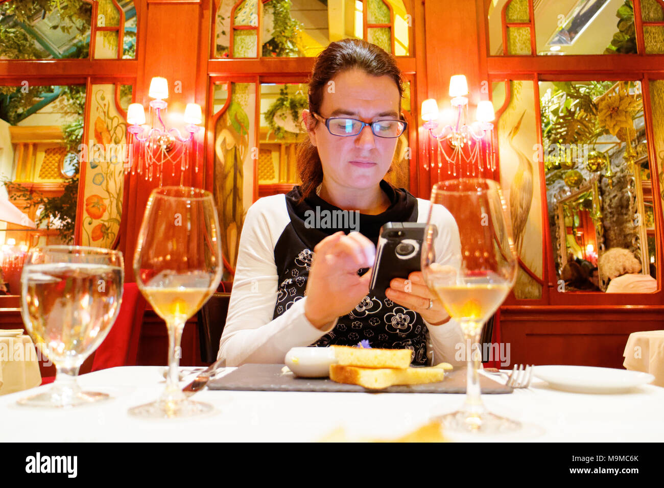 A woman seated using her mobile phone in the exclusive Saint Amour restaurant in Quebec City - Stock Image