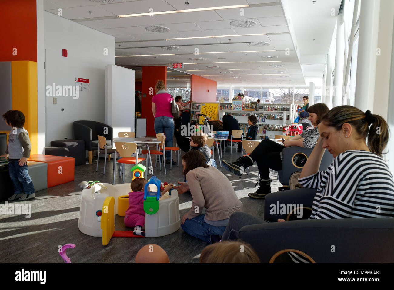 Mums with their children in a play area inside a public library in Quebec City, Canada - Stock Image