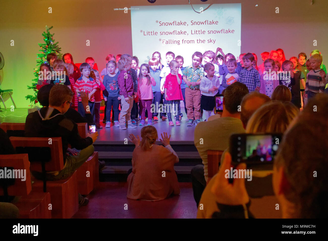 Infants singing their christmas song on stage with parents filming using their mobile phones - Stock Image