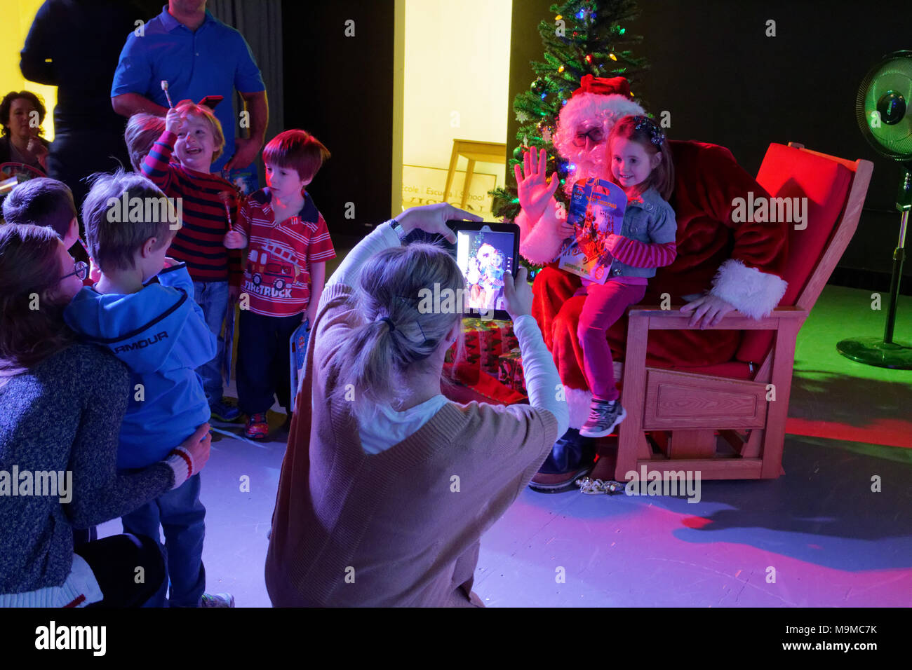 A mother using an ipad to photograph a child sat with Father Christmas - Stock Image