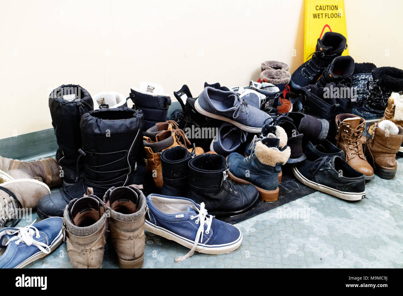 An untidy pile of shoes and  winter boots - Stock Image