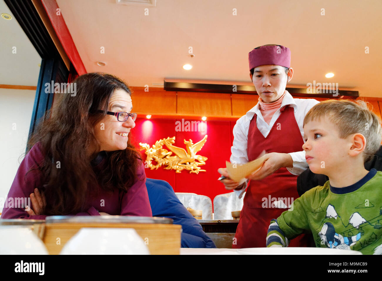 A mother beaming at her five year old son as dim sum dishes are served in a chinese restaurant - Stock Image