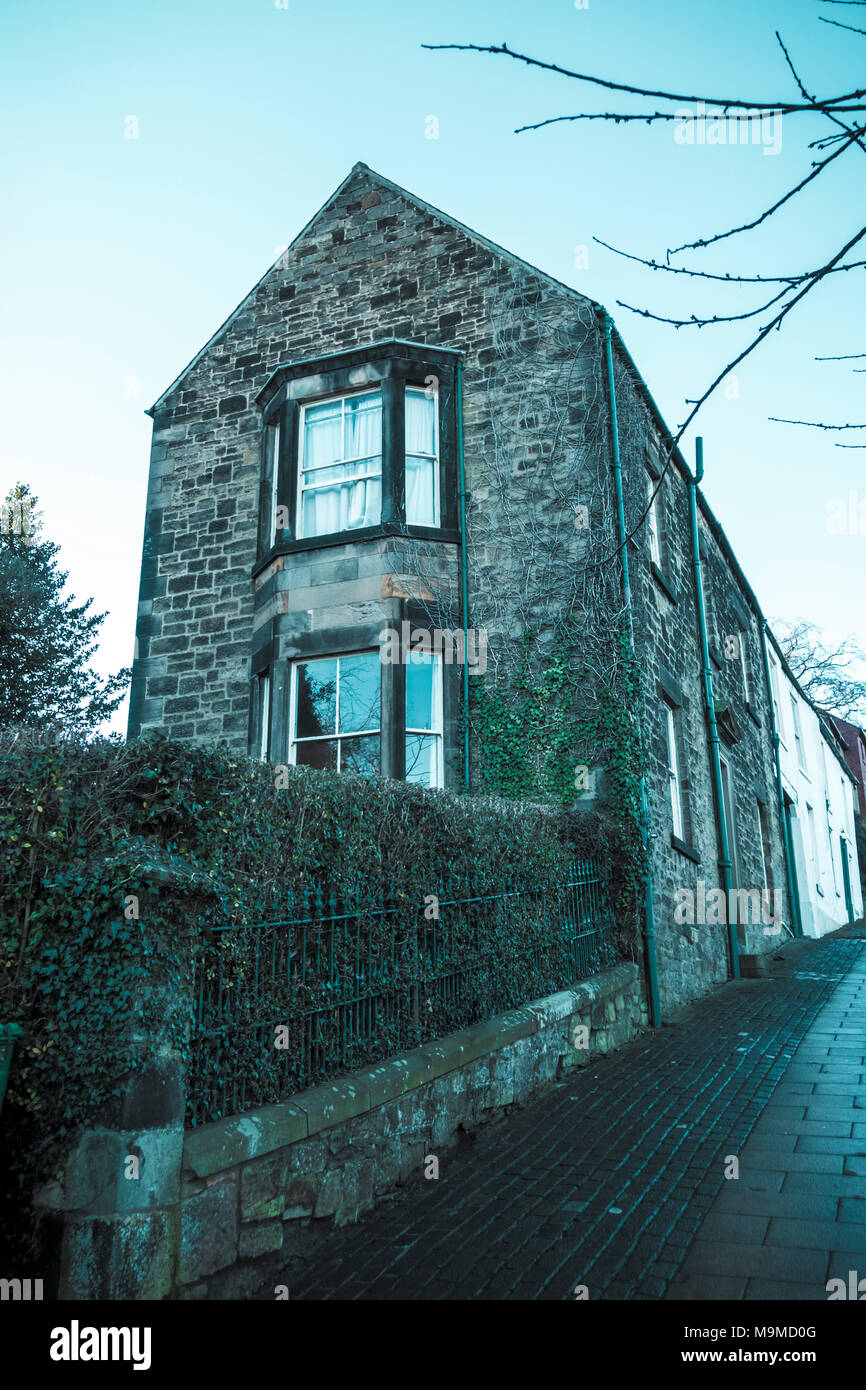 Bay windows in the gable end of a large stone building - Stock Image
