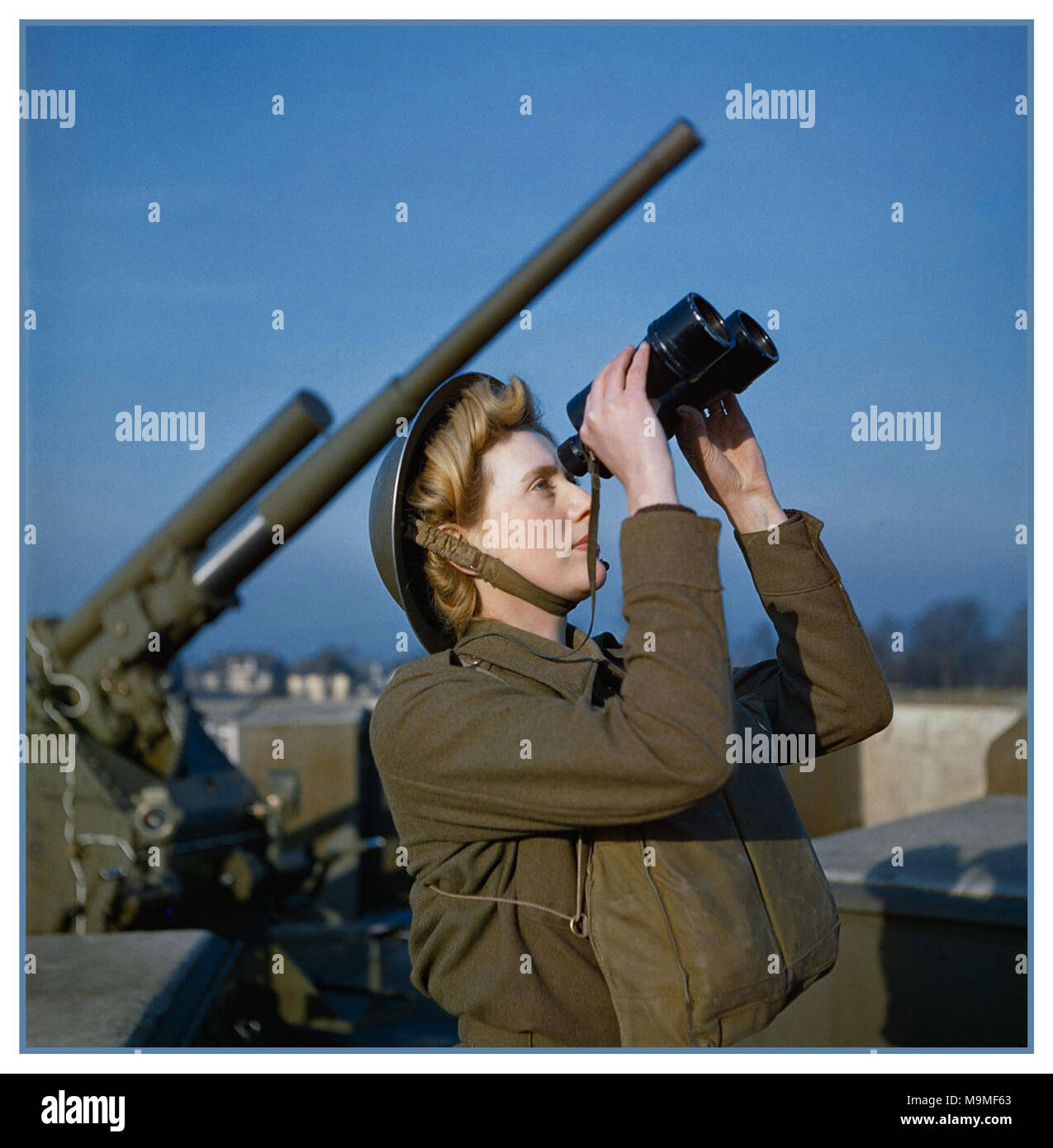 1940's WW2 December 1942 A British Auxiliary Territorial Service (ATS) 'spotter' at a 3.7-inch anti-aircraft 'ack ack' gun site searching for visual signs of Nazi Germany enemy aircraft or flying bombs - Stock Image