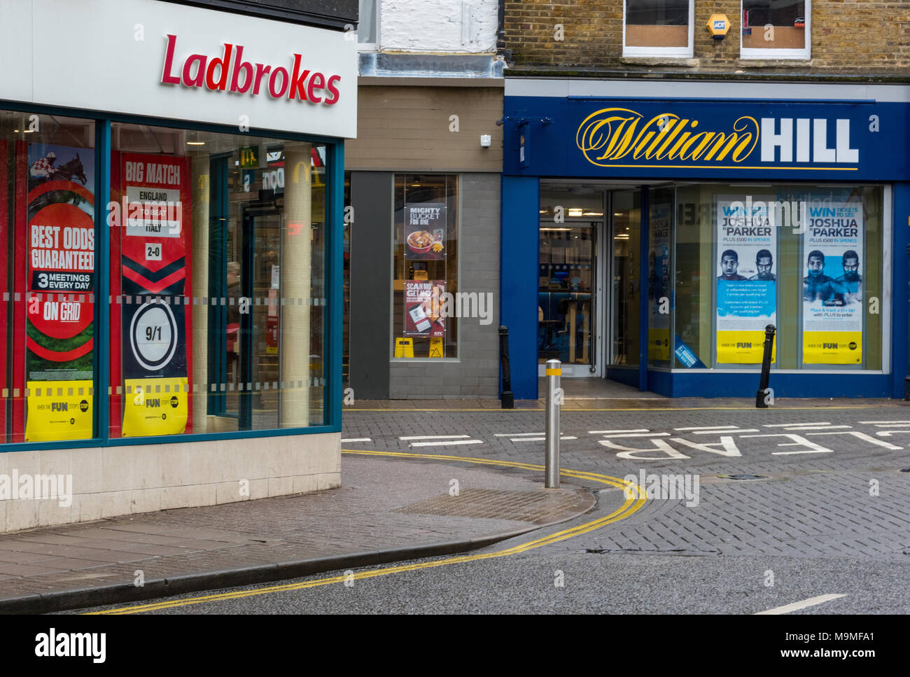 Betting shops or bookies premises in the high street for gamblers and gambling money and horse racing football odds. Addictions and bad habits money. - Stock Image