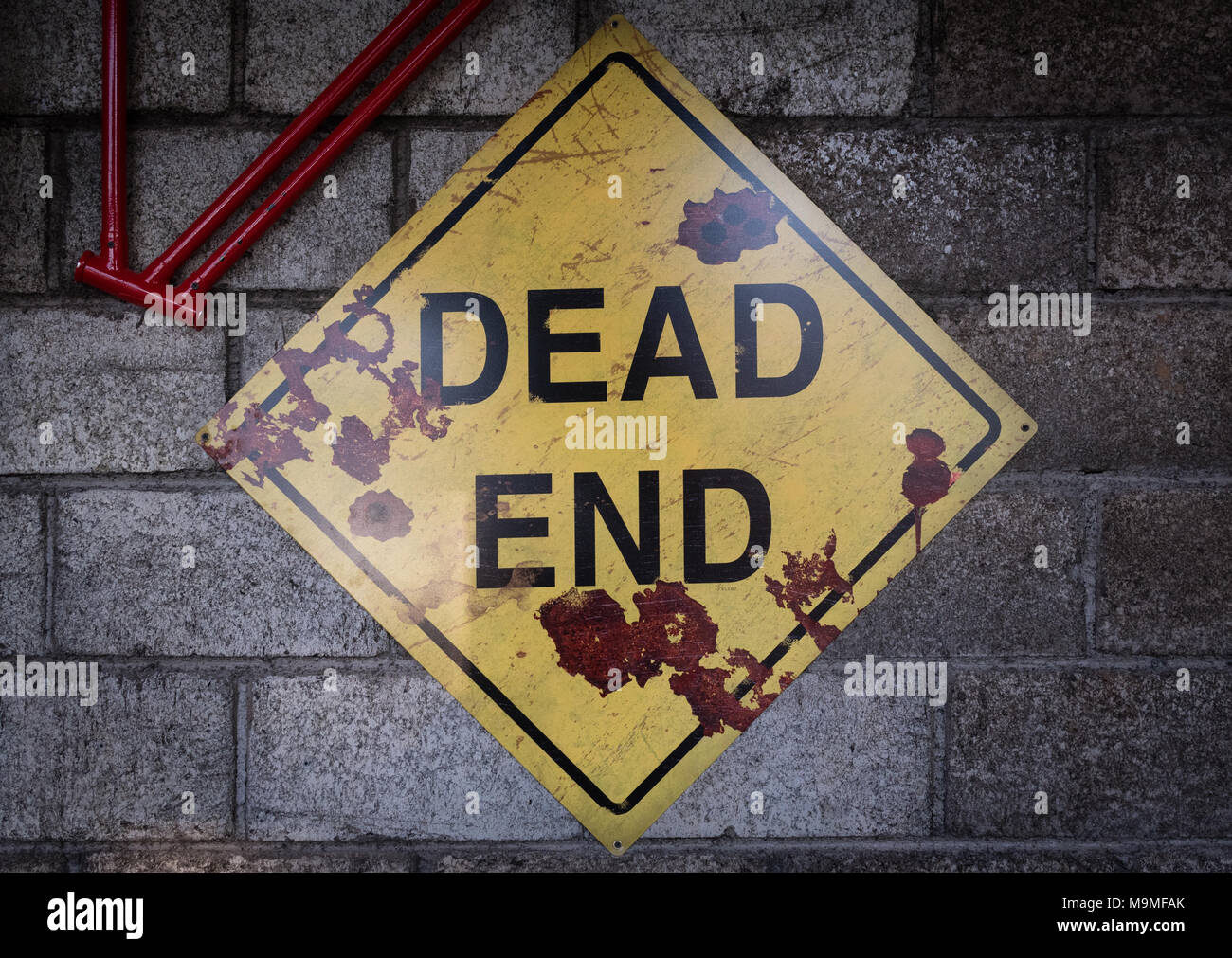 Weathered sign Dead End on the wall in workshop - Stock Image