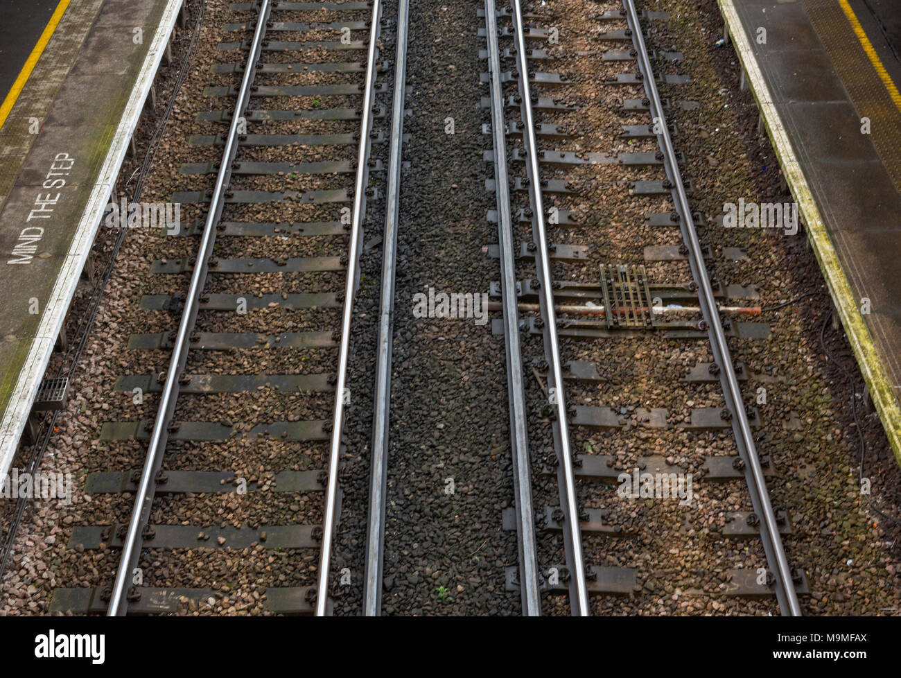 Looking down onto a railway tracks or lines at a station between the passenger platforms. Two railway lines tapering into the distance with edges line Stock Photo