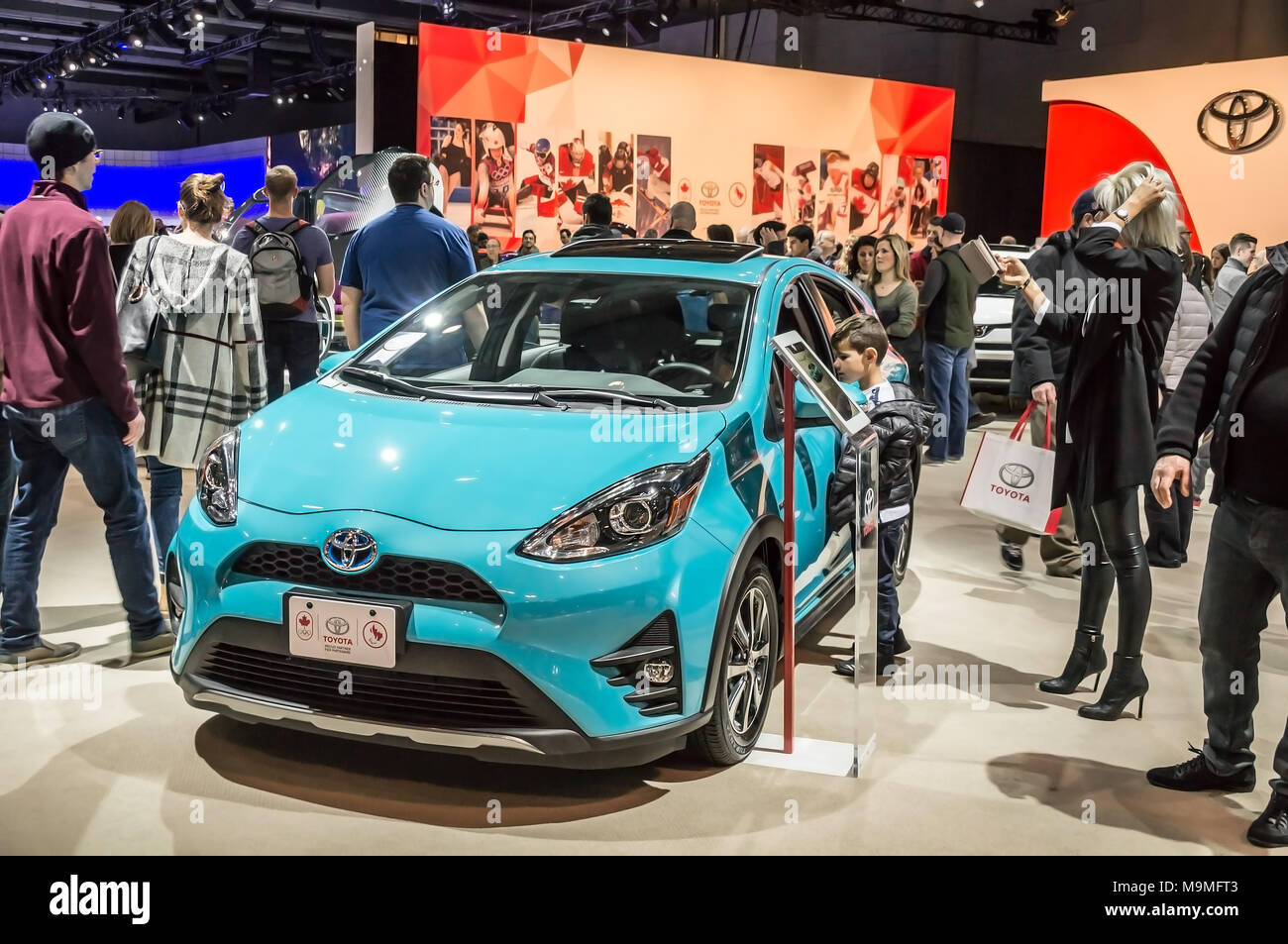 Toronto, Canada - 2018-02-19: Visitors of 2018 Canadian International AutoShow around the Prius c subcompact hybrid car on Toyota Motor Corporation exposition - Stock Image