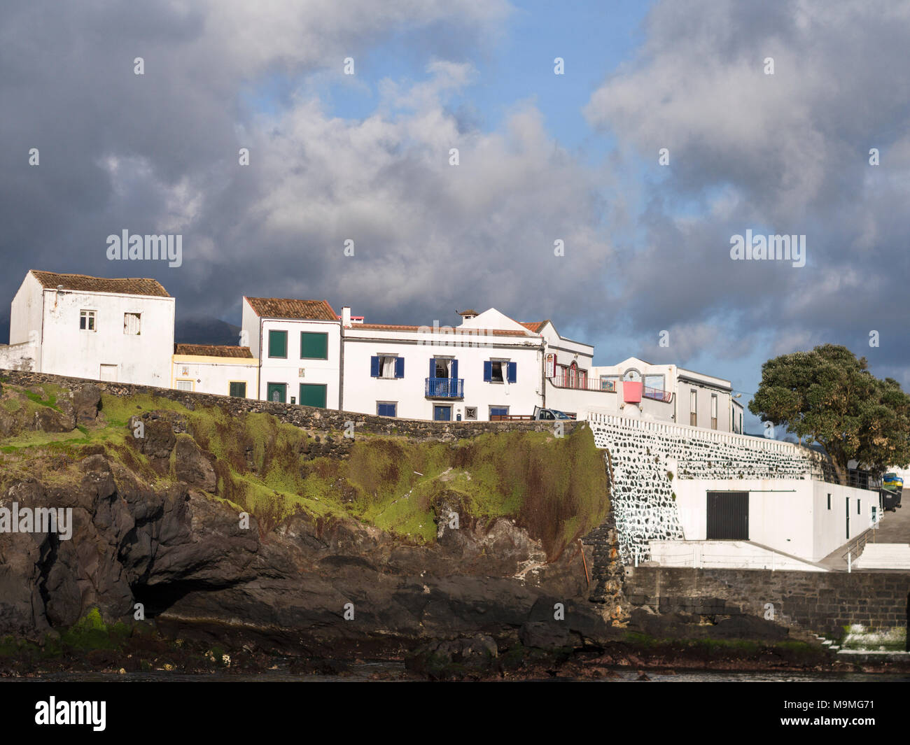 Whitewashed Coastal houses with Seawall: White houses line the coastal road and seawall around the port of Lagoa. Clouds pour in from the hills beyond. - Stock Image