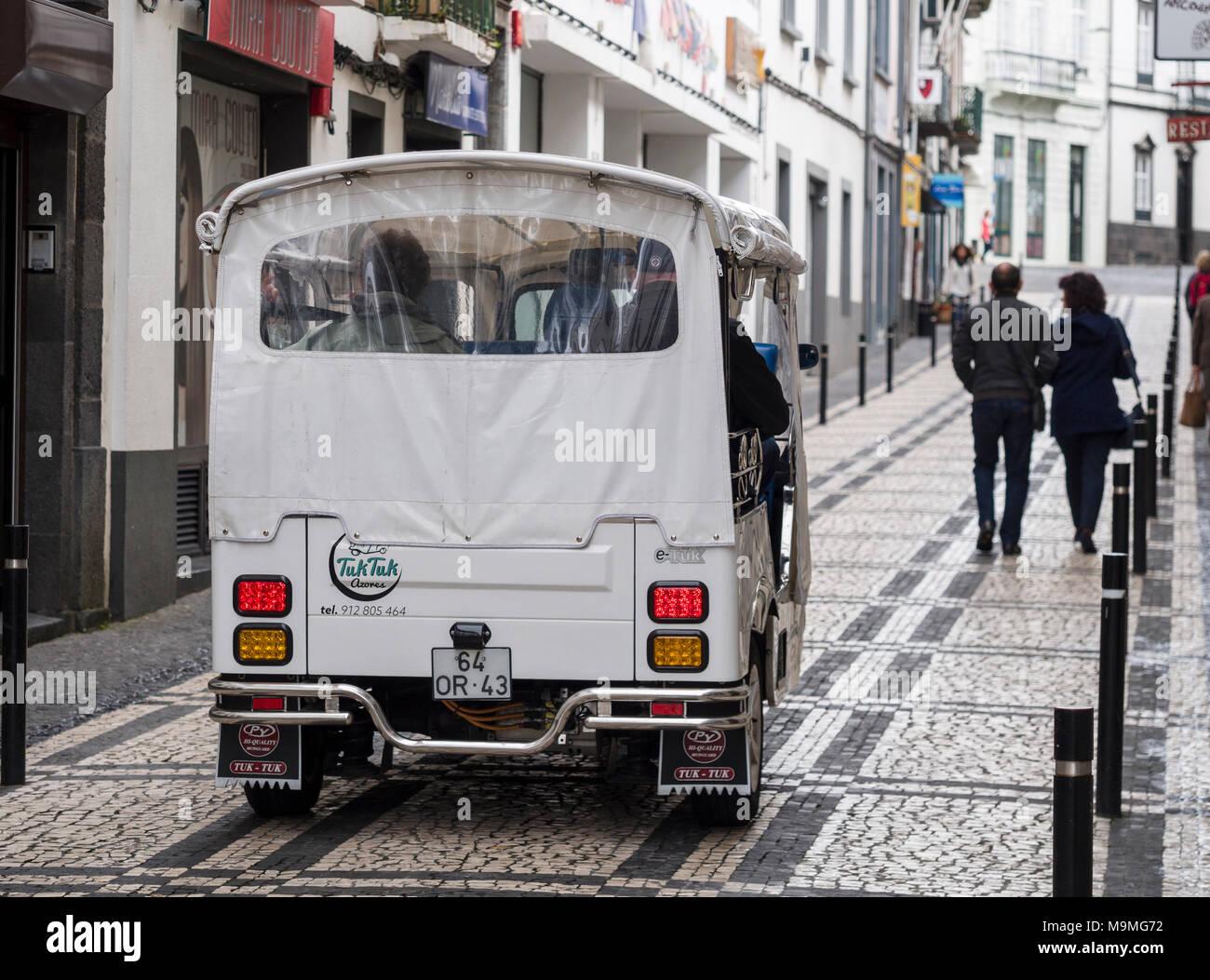 Tuk Tuk Azores: A small 3 wheeled motorbike ferries passengers on the narrow cobbled streets of Ponta Delgada. - Stock Image