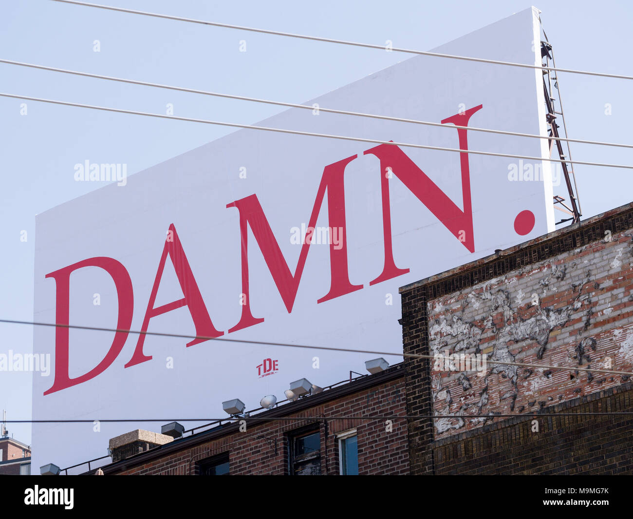 DAMN. Gardner Expressway visible billboard: A large billboard with the single word damn in large red letters graces an old building in Old Toronto. It is an ad for a new Kendrick Lamar album. - Stock Image
