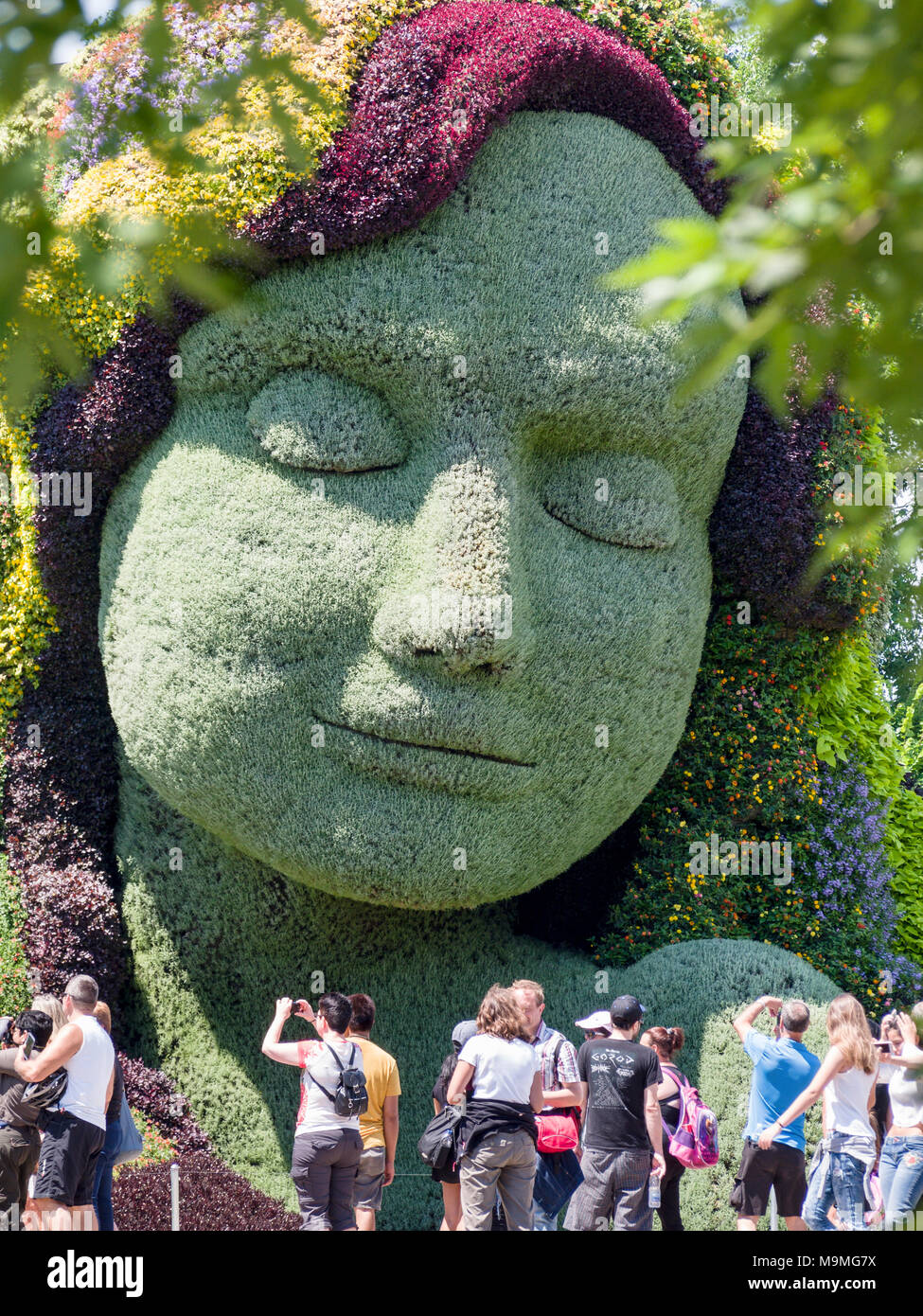 Mother Earth and Tourists: A huge plant-based sculpture of the face of Mother Earth with a gaggle of photographing tourists in front at MosaiCanada 150. - Stock Image
