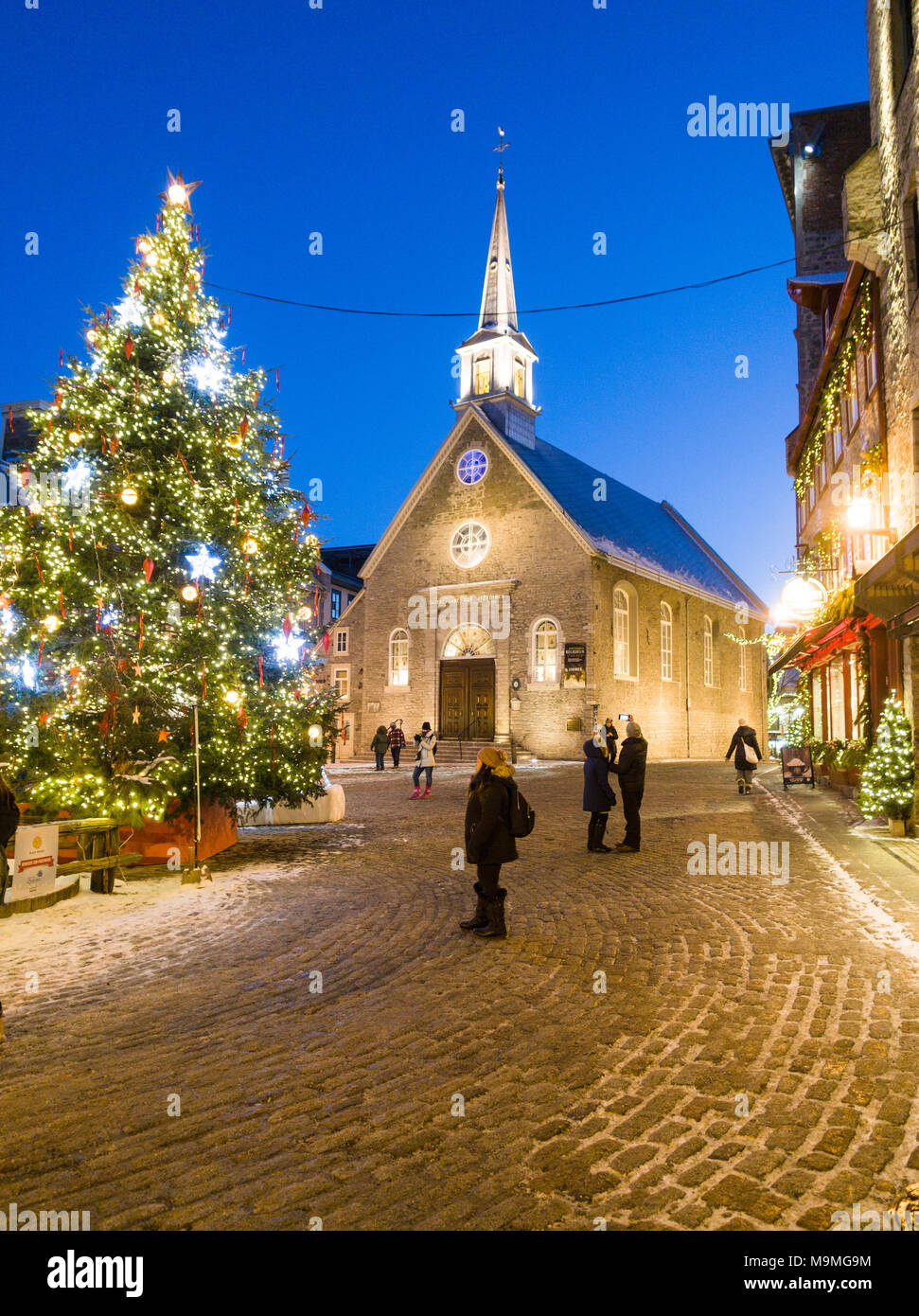 Notre Dame des Victorires and Christmas Tree: The small church in the touristic section of Lower Quebec with a large lit christmas tree in the square. Tourists watch and wander. - Stock Image