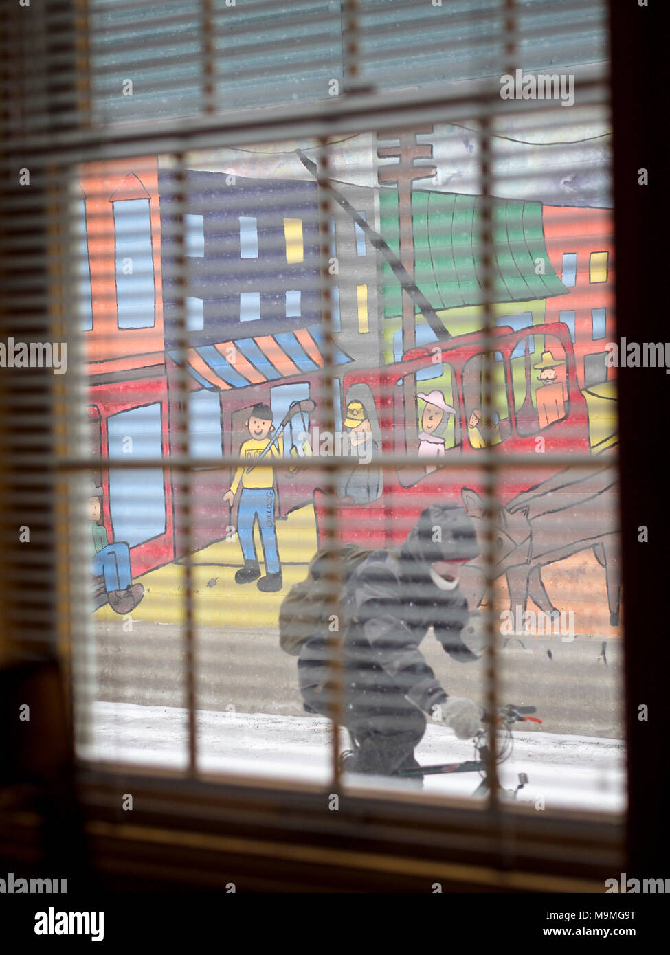 A cyclist rides by a bright mural as viewed through a window: A naive style mural decorates a wall on a small Quebec City street.  A bicyclist rides by as seen through a pained, blinded window on a snowy cold day. - Stock Image