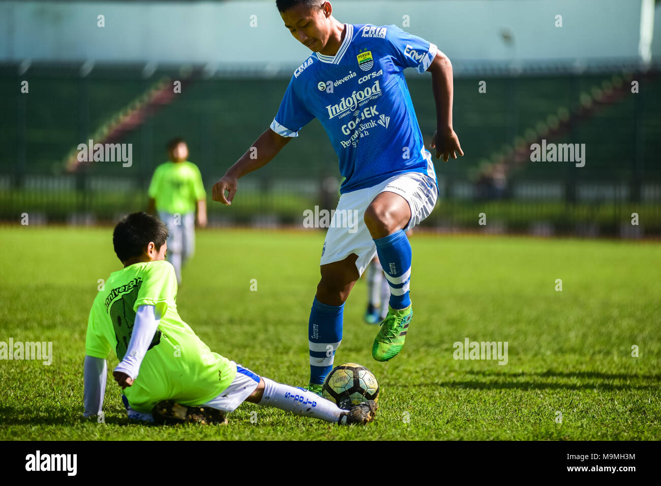 A child launches a sliding tackle on adult player during a friendly game to celebrate the 85th anniversary of Persib FC in Bandung, Indonesia. - Stock Image