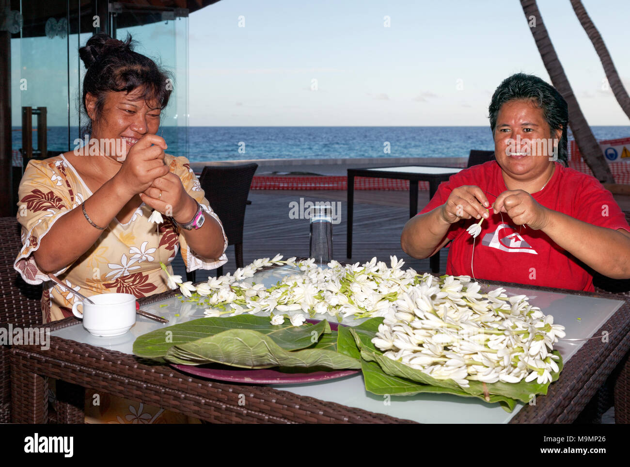 Two women, Polynesian, threads white blossoms, flowers to necklaces, Rangiroa, society islands, Windward Islands - Stock Image