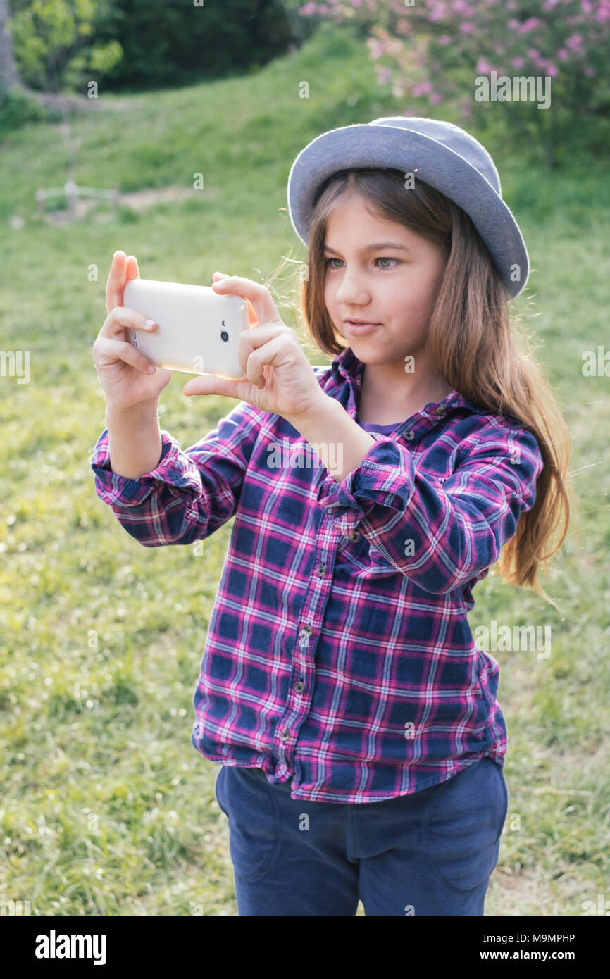Adorable pre-teen tweenie brunette kid girl with her smartphone in the spring park. Dressed in shirt and blue hat - Stock Image
