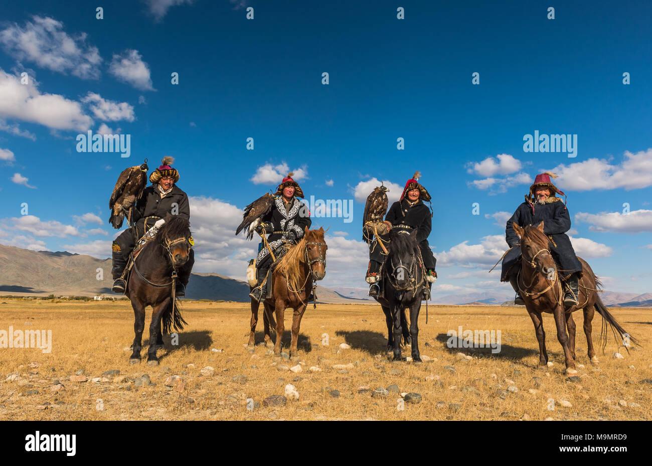 Mongolian eagle hunters on horses in the desert, Mongolia - Stock Image