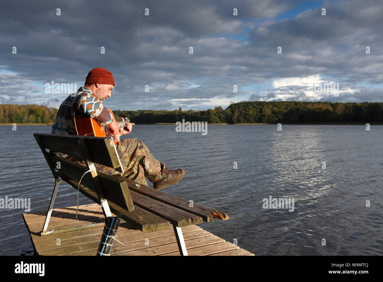 Man plays guitar on a boat landing stage at the lake, Mecklenburg Lake District, Mecklenburg-Western Pomerania, Germany - Stock Image