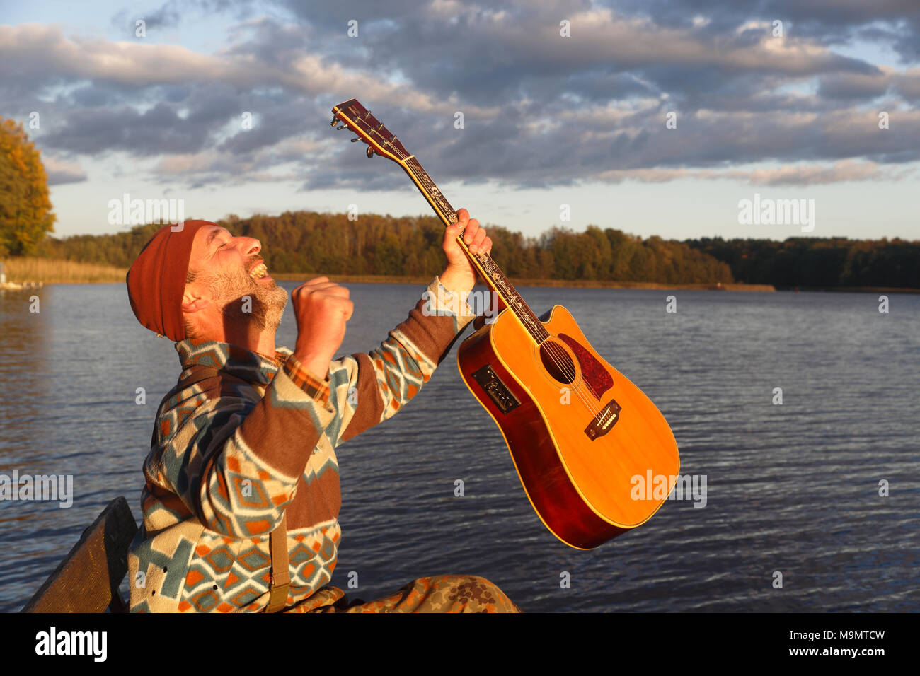 Man plays guitar on a boat landing stage at the lake and is pleased, Mecklenburg Lake District, Mecklenburg-Western Pomerania - Stock Image