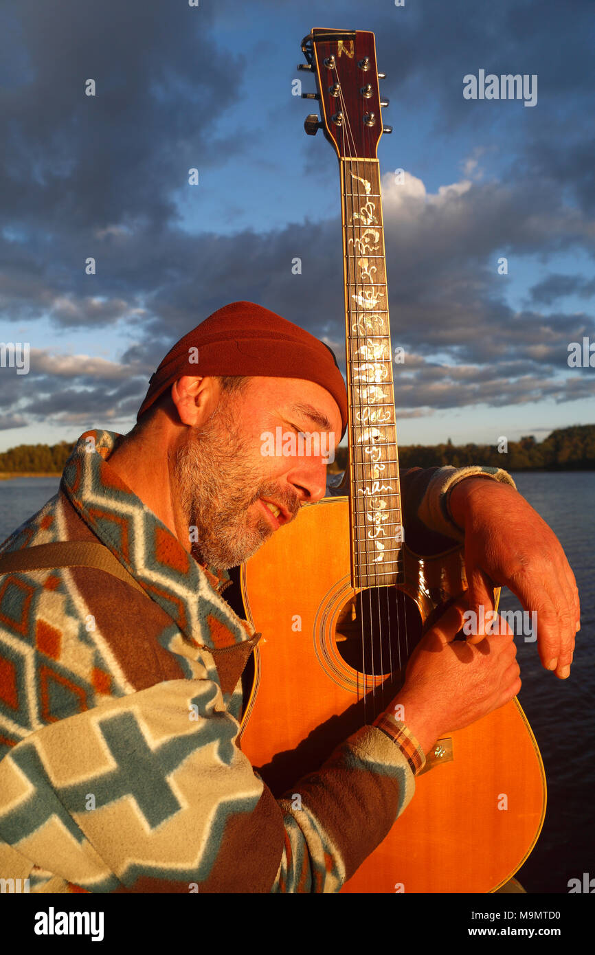 Man with guitar on a jetty at the lake, Mecklenburg Lake District, Mecklenburg-Western Pomerania, Germany - Stock Image