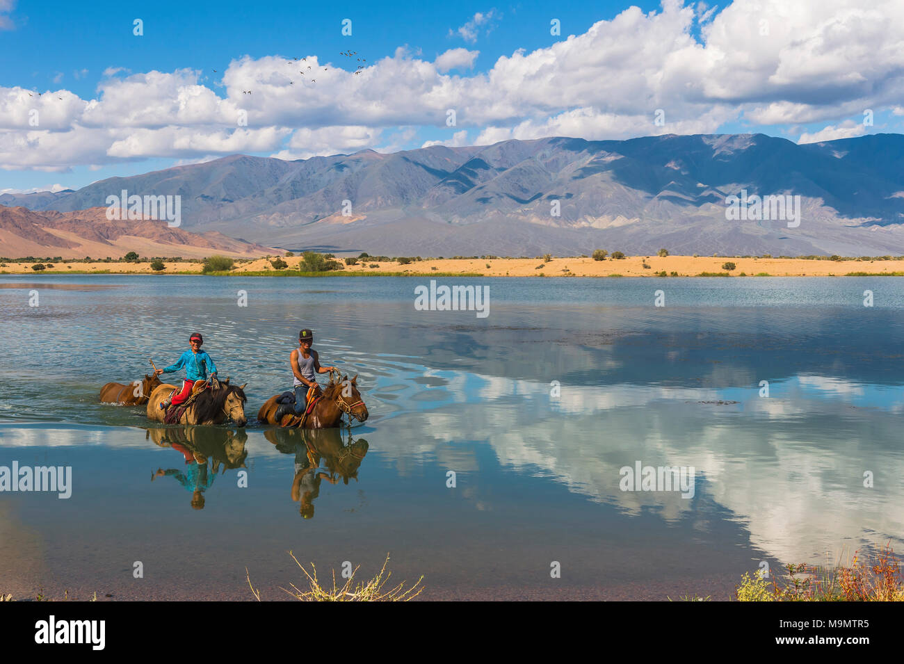 Nomad kids on horses crossing the Tuul river during summer time, Gorkhi-Terelj National Park, Mongolia - Stock Image