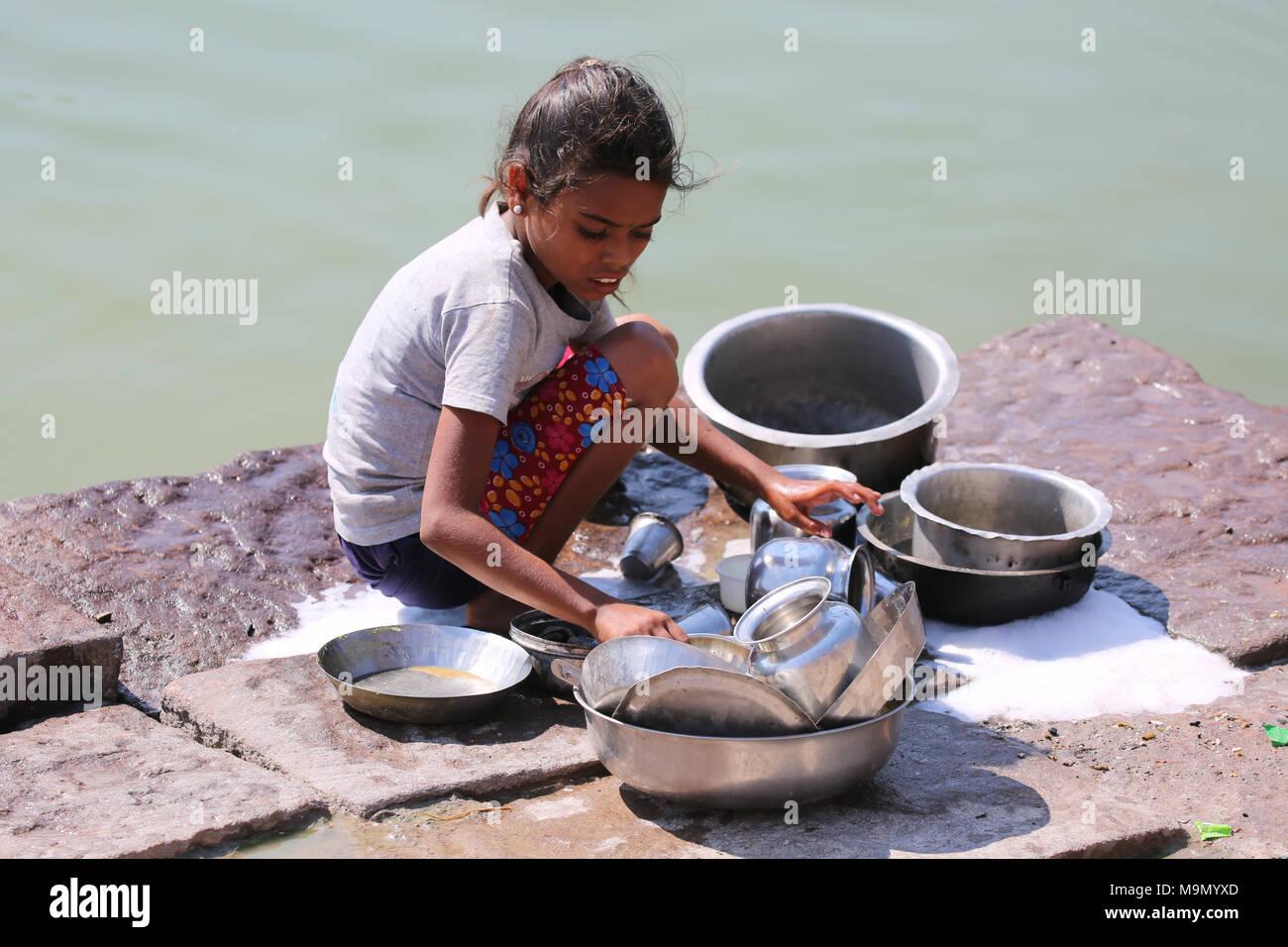 Indian girl washing dishes at the river -  indisches Mädchen beim Gechirr waschen am Fluss Stock Photo