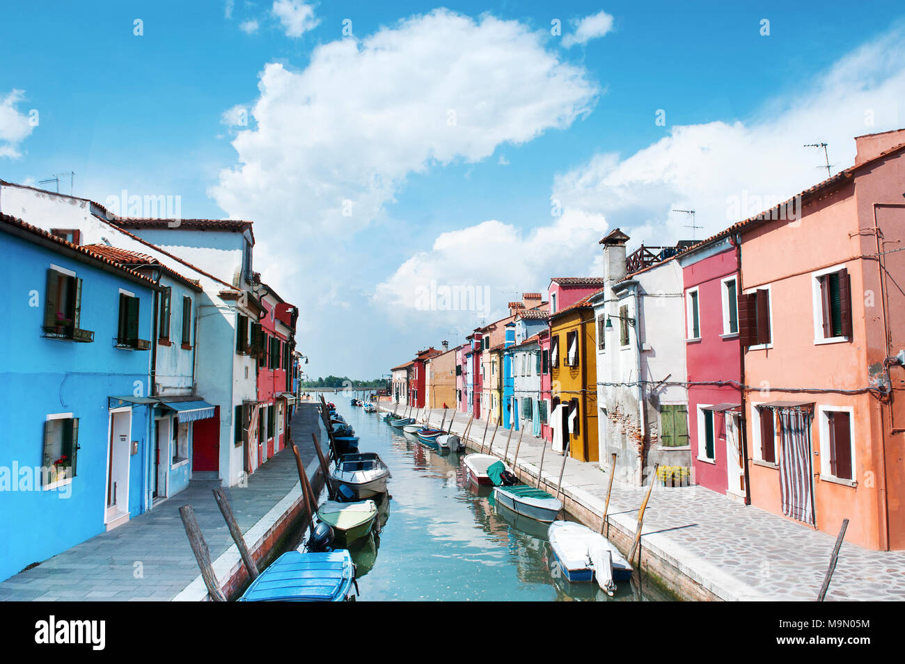 Burano island, Italy - beautiful view of a street with colorful houses and canal in a summer day. Venice postcard - Stock Image