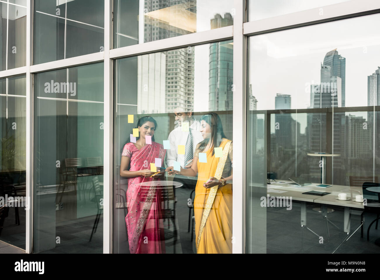 Indian employees sticking reminders on glass wall in the office - Stock Image