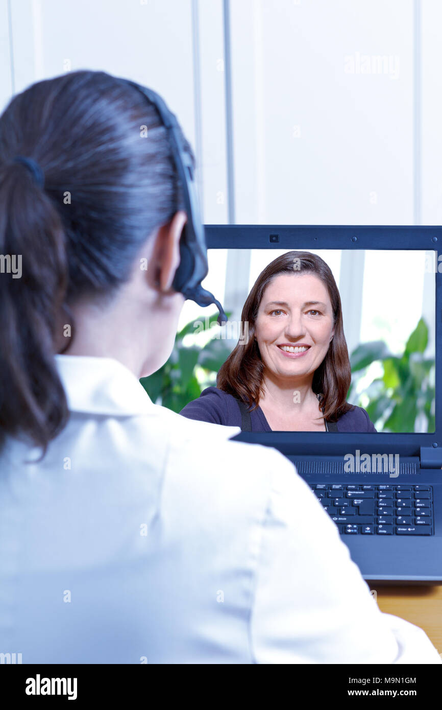 Physician with headset in front of her laptop during an online consultation with a middle aged female patient, telemedicine or e-health concept Stock Photo