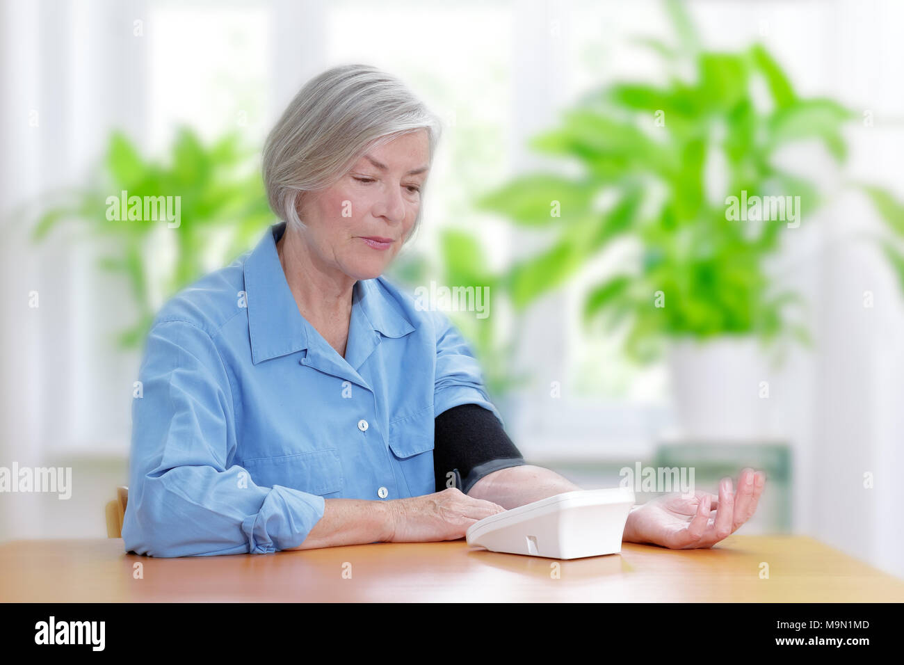 Senior woman suffering from hypertension sitting at a table in her living room measuring her blood pressure Stock Photo